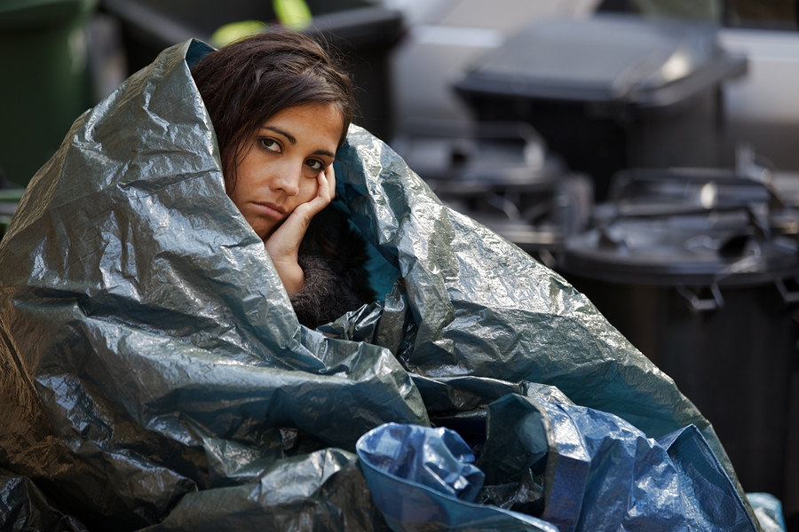 Homeless young woman wrapped in plastic